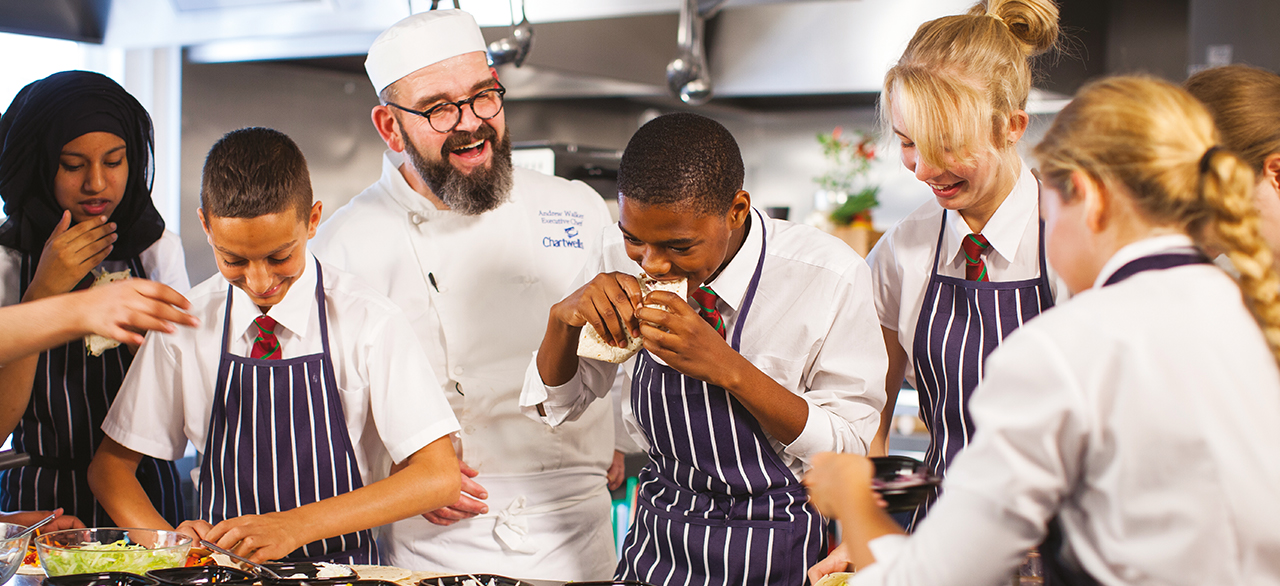 A team of chefs laughing and tasting food