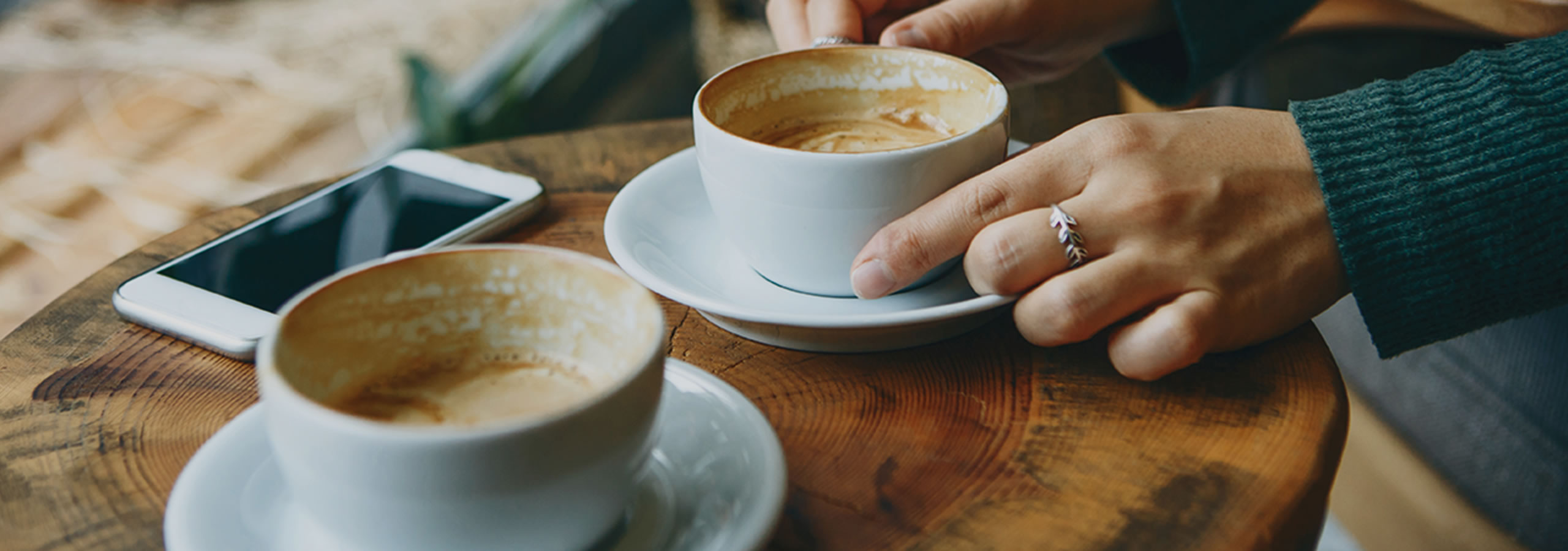 Hands holding a coffee cup in a café with a phone nearby